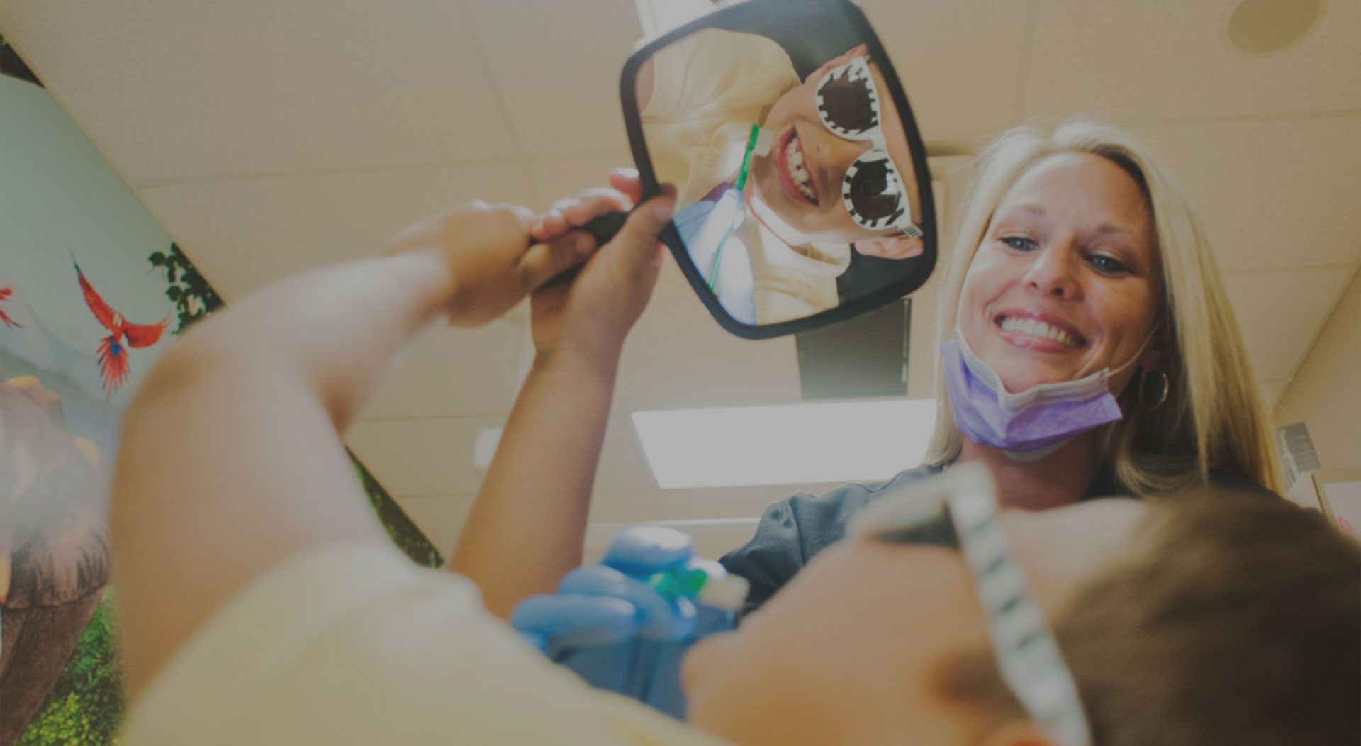 Child with mirror at Holdbrook Pediatric Dental